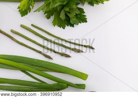 Parsley, asparagus and spring onion on white background. fresh produce green vegetables healthy eating organic food preparation concept.
