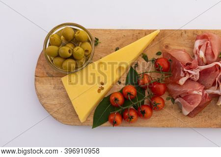 Olives, cheese, ham and cherry tomatoes on wooden board on white background. fresh produce appetizers healthy eating organic food preparation concept.