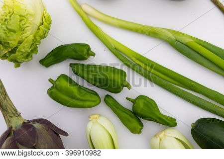 Lettuce, peppers and spring onion on white background. fresh produce green vegetables healthy eating organic food preparation concept.