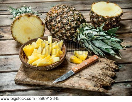 Sliced Pineapple In A Bowl On A Cutting Board With A Knife And A Whole Pineapple. On Wooden Backgrou