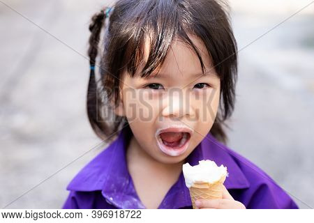 Little Girl Was Eating A White Ice Cream Cone. Child Messed Up His Mouth For Dessert. Children Smile