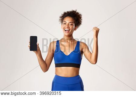 Sport And Technology Concept. Cheerful African-american Fitness Woman Showing Workout App On Smartph