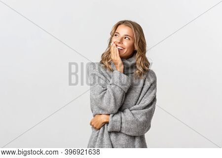 Portrait Of Attractive Caucasian Woman In Grey Sweater Looking At Logo At Upper Left Corner, Smiling