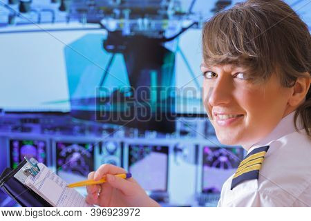 Beautiful woman pilot wearing uniform with epauletes, writting on notepad inside airliner