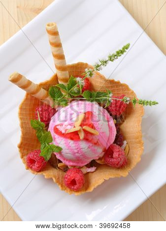 ice cream sundae with biscuit sticks, fresh raspberries and salvia, in the waffle bowl