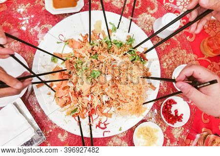 People Preparing To Toss Yusheng Or Yee Sang, A Dish Consumed During Chinese New Year For Luck And P