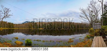 Beautiful Lake Reflecting Blue Sky Like A Mirror, Rolling Mountain Range And Woodland In The Backgro