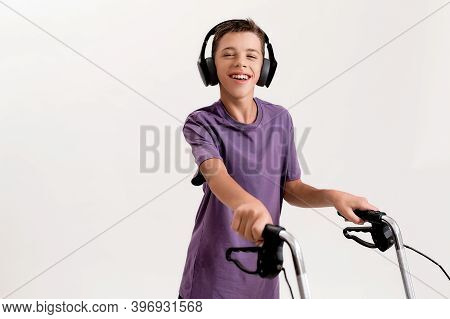 Portrait Of Happy Teenaged Disabled Boy With Cerebral Palsy In Headphones Smiling At Camera, Taking
