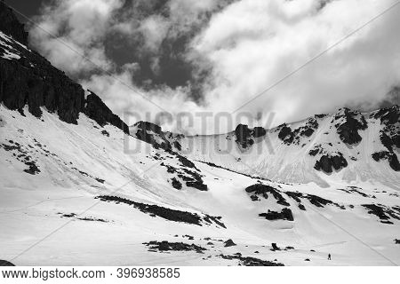 High Mountains With Snow Cornice And Avalanche Tracks, Snowy Plateau And Cloudy Sunlit Sky At Sunny