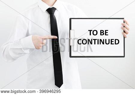 A Businessman Holds A Folder With Documents, The Text On The Folder Is - To Be Continued. Business C