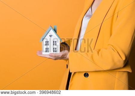 Take A Mortgage, Lending For The Purchase Of Real Estate. A Young Woman With A Small House In Her Ha