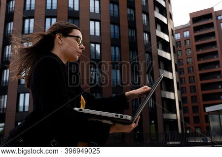 Young Woman In A Coat Looks At An Open Laptop, A Portrait Of A Business Woman Against The Background