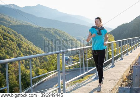 Young Woman Went For A Morning Jog, Healthy Lifestyle, Athlete Runs On The Road In The Mountains