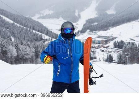 Close Up Portrait Guy Holding Orange Snowboard In Winter. Snowboarder In Blue Jacket With Snowy Moun