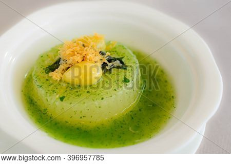 Main Course Of Simmered Winter Melon In Spinach Sauce Topped With A Gingko Nut Served In A White Bow