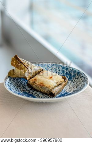 Main Course Of Glutinous Rice With Scallops Wrapped In Lotus Leaves Served On A Beautiful Porcelain