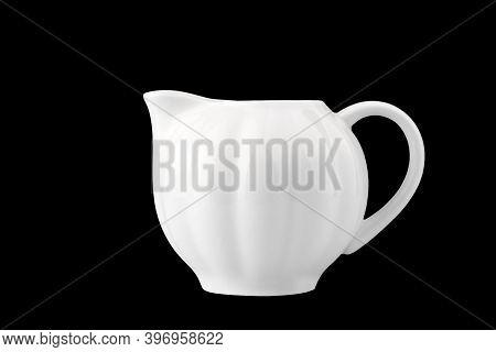 White Porcelain Creamer, Isolate On A Black Background