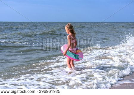 Summer Landscape Girl 5 Years Old Blonde Stands On The Seashore With A Lifebuoy.