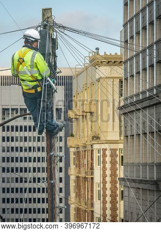 Lineman (or Lineworker Or Engineer) In A City (san Francisco) Fixing A Telephone Line