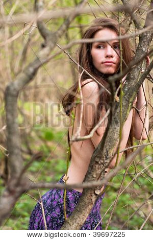Fashion portrait of young naked woman in the forest