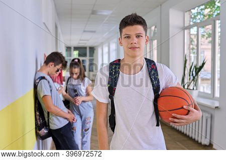 Portrait Of Student Teenager Guy 16, 17 Years Old With Basketball Ball Backpack In School Building,