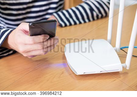 Selective Focus At Internet Router With Man Using Smart Phone Device To Connect To Internet Or Wirel