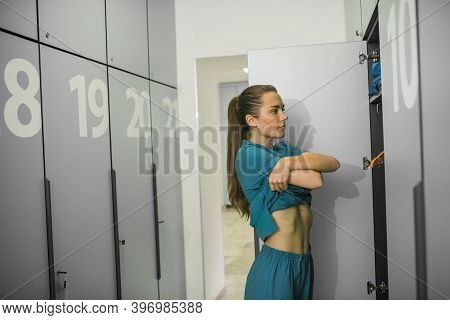 Long-haired Young Female Doctor Changing Clothes In The Locker Room