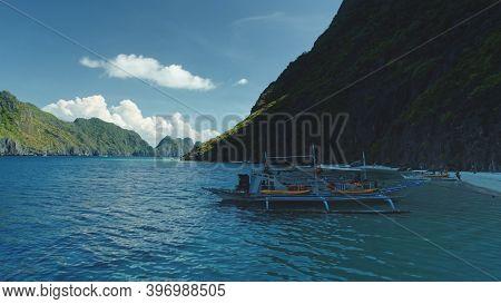 Closeup passengers boats at ocean coast with cliff shore at summer tour. Serene tropical nature scape at mountain island of Palawan, Philippines, Visayas Archipelago. Cinematic close up drone shot
