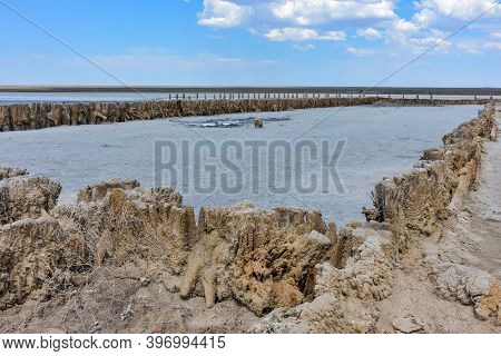 Stunning, White Salt Desert Or Salt Lake. Remains Of A Wooden Building In A Salt Lake. Dried Up Salt