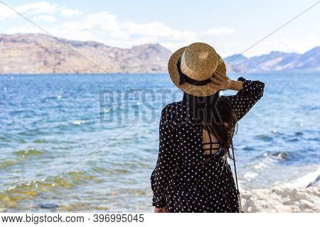 Young Woman Wearing A Straw Hat Gazing Out Onto Okanagan Lake In British Columbia, Canada. Optimisti