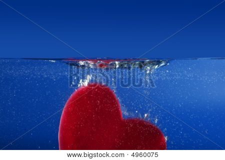 Candy Red Heart Shape Sinking Into The Blue Water