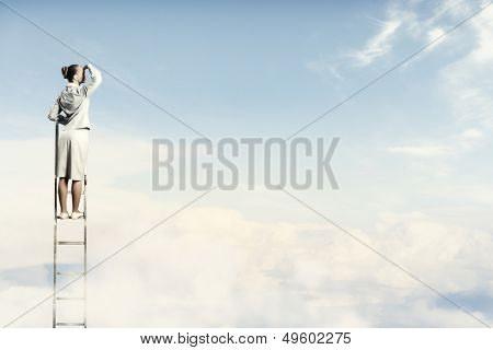 Businesswoman standing on ladder looking into distance against cloudy background
