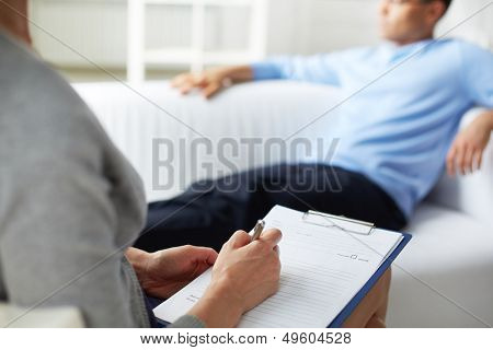 Female psychologist making notes during psychological therapy session