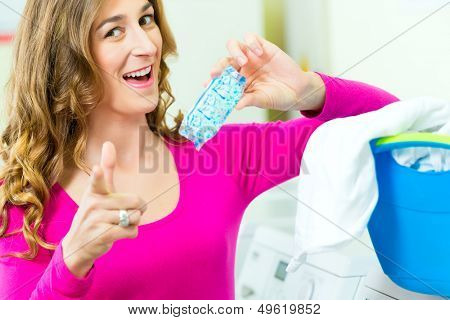 Young woman with laundry basket and detergent in a laundrette she washed their laundry clean and is happy about it