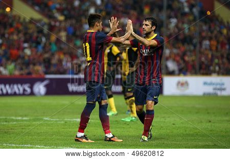 KUALA LUMPUR - AUGUST 10: Barcelona's Neymar (left) and Cesc Fabregas celebrate a goal scored against Malaysia at the Shah Alam Stadium on Aug 10, 2013 in Malaysia. FC Barcelona wins 3-1.