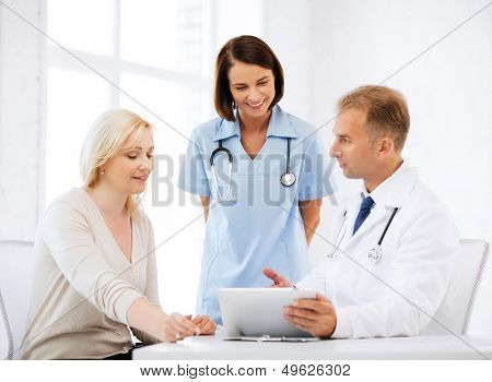 healthcare, medical and technology - doctor showing something to patient on tablet pc