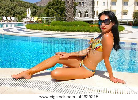 beautiful brunette near the swimpool