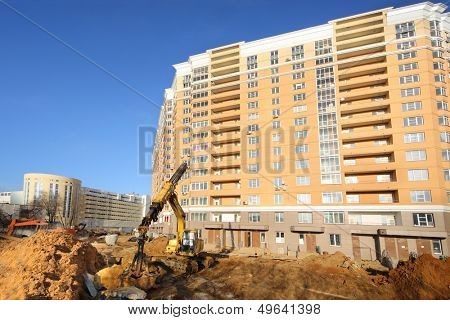 Dredger digs ground near high multi-storey yellow building under construction at sunny day.
