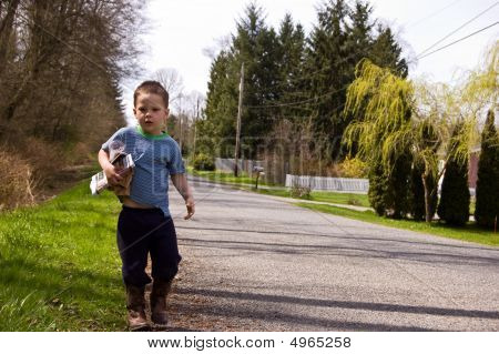 Little Boy Picking Up Litter On Roadside