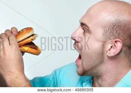 Funny man eating hamburger on grey background