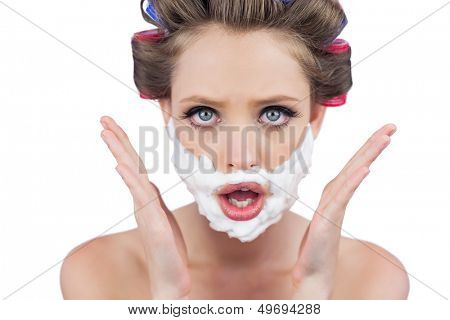 Astonished woman posing with shaving foam on face on white background