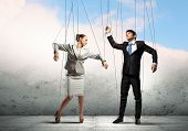 Image of businesspeople hanging on strings like marionettes. Conceptual photography poster