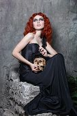 Red-haired vampire girl posing with a skull in her hands in urban twilight poster