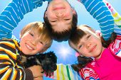 Circle of three happy children with their dog. poster