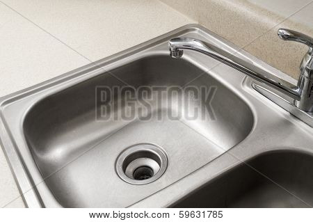 Horizontal shot of an empty stainless steel kitchen sink shot close up with chrome faucet. poster