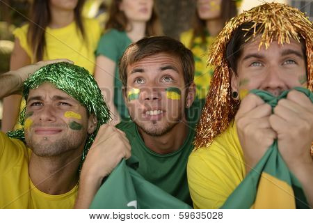 Astonished group of Brazilian sport soccer fans looking at the screen.