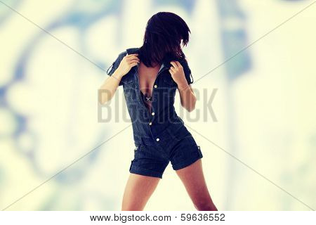 Sexy, beautiful, young woman dancing (hair flying) in jeans siut