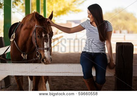 Pretty Hispanic young woman petting and having fun with a horse in a ranch poster
