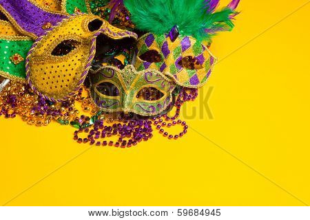 A festive, colorful group of mardi gras or carnivale mask on a yellow background.  Venetian masks. poster