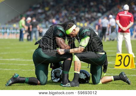 VIENNA,  AUSTRIA - APRIL 21 QB Jonathan Dally (#8 Dragons) and RB Tunde Ogun (#1 Dragons) pray before the AFL football game on April 21, 2013 in Vienna, Austria.